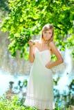 Junge künstlerische Frau mit Blumen draußen Lizenzfreie Stockfotografie