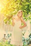 Junge künstlerische Frau mit Blumen draußen Stockfotografie