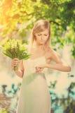 Junge künstlerische Frau mit Blumen draußen Stockfotos