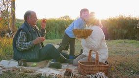 Junge küsst den Großvater, der auf Plaid mit Hund und Igelem am Picknick auf Hintergrund der Natur sitzt stock video footage
