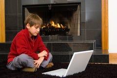 Junge am Kamin auf Computer. Lizenzfreie Stockfotografie
