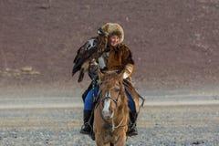 Junge kasachische Eagle Huntress Berkutchi-Frau mit Pferd bei der Jagd zu den Hasen mit von Steinadlern auf seinen Armen Stockbild