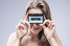 Junge kaukasische blonde Frau, die Audiokassette in der Front hält Stockfoto
