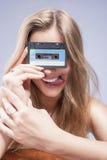 Junge kaukasische blonde Frau, die Audiokassette in der Front hält Stockbilder