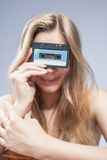Junge kaukasische blonde Frau, die Audiokassette in der Front hält Lizenzfreie Stockbilder
