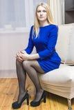 Junge kaukasische blonde Frau im blauen Kleid, das zuhause auf Couch aufwirft Stockbilder