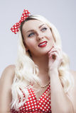 Junge kaukasische blonde weibliche Aufstellung in der Pinup-Art gegen Weiß Stockfotografie