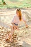 Junge kaukasische blonde weibliche Person, die auf Weidenhängematte, Sandhintergrund sitzt Lizenzfreies Stockbild