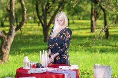 Junge kaukasische blonde weibliche Umhüllungs-Tabelle draußen installiert Stockfotografie