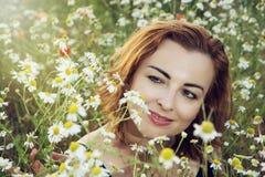 Junge kaukasische Brunettefrau in der Gänseblümchenwiese Lizenzfreie Stockfotografie