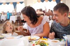 Junge kaukasische Familie, die zusammen zu Abend isst Lizenzfreie Stockfotografie