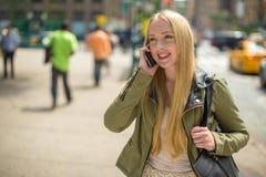 Junge kaukasische Frau auf Mobiltelefon in der Stadt Stockfoto