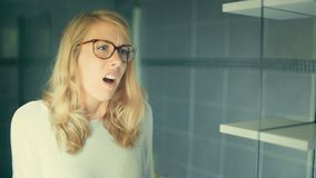 Junge kaukasische Frau, die auf den Gläsern unglücklich mit ihrer Reflexion versucht stock video
