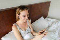 Junge kaukasische Frau, die drahtlose Kopfhörer verwendet und Musik durch Smartphone hört stockfotografie