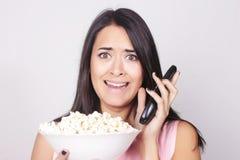 Junge kaukasische Frau, die einen Film/Fernsehen aufpasst Lizenzfreies Stockfoto