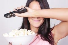 Junge kaukasische Frau, die einen Film/Fernsehen aufpasst Lizenzfreie Stockbilder