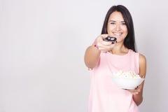 Junge kaukasische Frau, die einen Film/Fernsehen aufpasst lizenzfreies stockbild