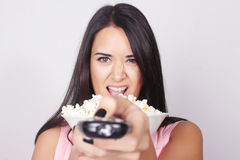 Junge kaukasische Frau, die einen Film/Fernsehen aufpasst stockbild