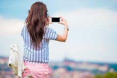 Junge kaukasische Frau, die Foto von der europäischen alten Stadt durch Handy vom Beobachtungsplatz macht Lizenzfreies Stockbild