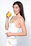 Junge kaukasische Frau, die Orangensaft trinkt Lizenzfreie Stockfotos
