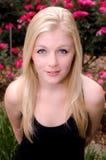 Junge kaukasische Frau, die Sie vor rosa Rosen betrachtet Stockfoto