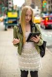 Junge kaukasische Frau, die Tablette in der Stadt verwendet Lizenzfreies Stockbild