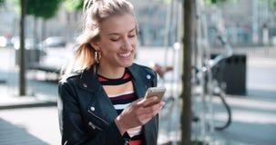 Junge kaukasische Frau, die Telefon in einer Stadt verwendet Lizenzfreie Stockbilder