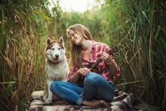 Junge kaukasische Frau, die Ukulele mit Schlittenhund spielt stockfotos