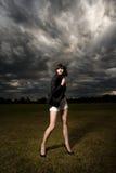 Junge kaukasische Frau in einem Park mit stürmischem Himmel Lizenzfreie Stockfotos