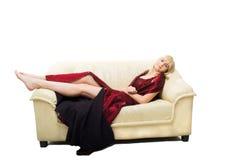 Junge blonde Frau auf Sofa Lizenzfreies Stockbild