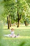 Junge kaukasische Frau im Hut, der Picknick auf Plaid mit Früchten im Park hat lizenzfreies stockbild