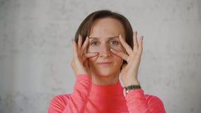 Junge kaukasische Frau im roten rosafarbenen Rollkragen bilden Gesichter vor Kameraabschluß stock footage