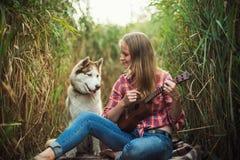 Junge kaukasische Frau mit dem Hund, der Ukulele spielt stockfotografie
