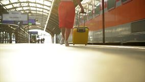Junge kaukasische Frau mit dem Koffer, der läuft, um den Zug herein zu erreichen, bevor er die Station ohne sie lässt stock video footage