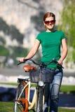 Junge kaukasische Frau mit ihrem Fahrrad Lizenzfreie Stockfotografie