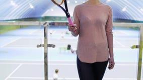 Junge kaukasische Frau mit Tennisschläger steht an unscharfem Hintergrund von Gerichten stock video