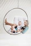 Junge kaukasische Frau mit zwei Babys, die Spaß haben stockfotografie