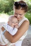 Junge kaukasische Frau und ihr Babysohn im Riemen lizenzfreie stockbilder
