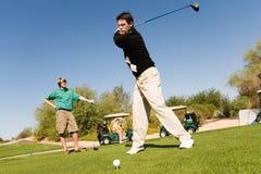 Junge kaukasische Freunde, die Golf spielen Lizenzfreie Stockfotografie