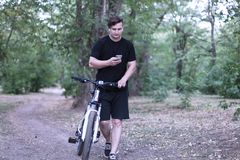 Junge kaukasische Mannbrandungen durch den Handy, der in den Park radfährt lizenzfreies stockfoto