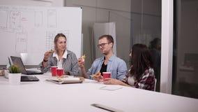 Junge kaukasische Mitarbeiter, welche die Mittagspause zusammen isst Pizza im Büro haben Lachen, sprechend und haben Spaß persona stock video