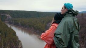 Junge kaukasische Paare, die am Abhang über dem Gebirgsfluss enjoing ist schöne Natur stehen stock video footage