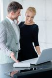 Junge kaukasische Paare, die angezeigten Laptop schauen Lizenzfreie Stockbilder