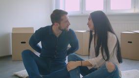 Junge kaukasische Paare, die auf Boden des neuen Hauses nahe den cardboxes spielen mit Schlüsseln und dem Küssen sitzen stock video