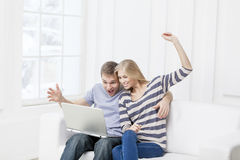 Junge kaukasische Paare, die auf Couch sitzen Lizenzfreies Stockbild