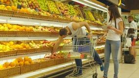 Junge kaukasische Paare, die in einen Supermarkt mit einer Marktlaufkatze gehen und frische Äpfel wählen Mann setzt Früchte stock video