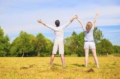 Junge kaukasische Paare, die zusammen auf Gras-Wiese mit ha stehen Stockbilder