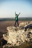 Junge kaukasische positive Frau, die auf dem hohen Felsen aufwirft Lizenzfreies Stockbild