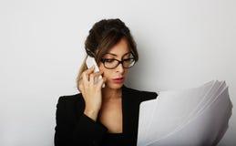 Junge kaukasische schöne weibliche Frau, die den Handy sitzt am Tisch über leerem weißem Studiohintergrund verwendet Lizenzfreie Stockbilder