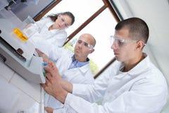 Junge kaukasische Wissenschaftler, die Molekülstruktur im Labor studieren Lizenzfreie Stockfotografie